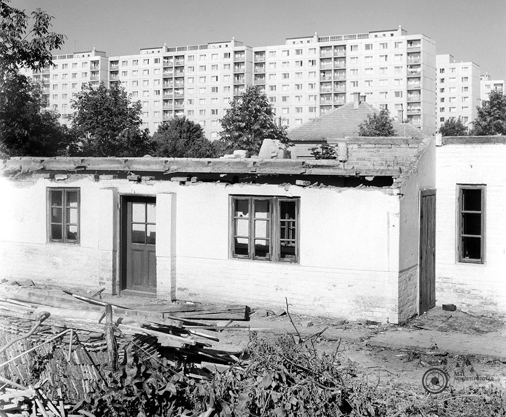 Szeged, 1973. május 29. Egy bontás alatt lévő régi, földszintes vályogház Szeged új lakónegyede, a Tarján városrészen épülő lakótelep tőszomszédságában. MTI Fotó: Kozák Albert<br />Szegeden az Odessza-telep után a második nagy lakótelep felépítésére a város északkeleti részén elhelyezkedő Tarjánt jelölték ki. Az építkezés 1966-ban indult téglablokkos technológiával. Ekkor ötszintes, gázfűtésű lakásokat építettek. 1968-ban Szegeden is elkezdték a panelházak építését. A Tarján városrészben 7418 lakásból 73% panel.