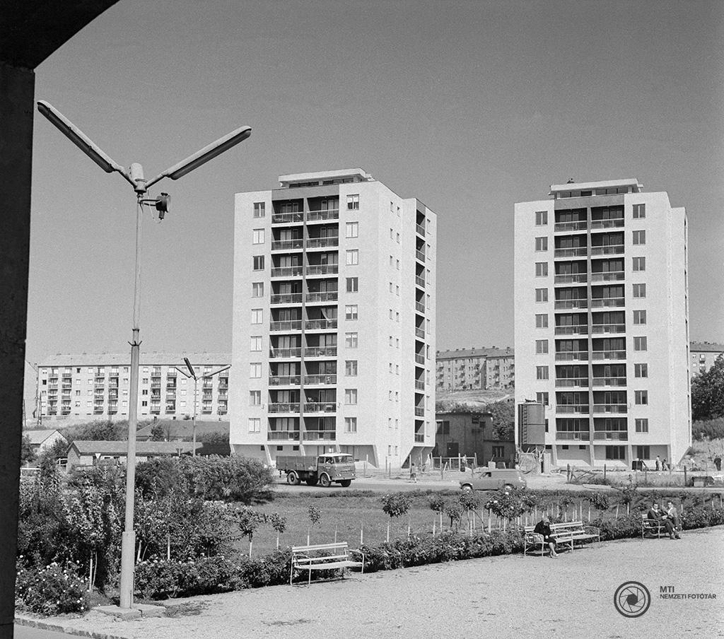 Komló, 1965. szeptember 3. A korabeli képaláírás: 'Új kilenc emeletes lakóházak az észak-baranyai város főterén. A bányászvárosban másfél évtizede kezdték meg a nagyarányú lakásépítkezést és azóta felépült a város ötvenedik új utcája is. Az új városnegyedben 1949 óta több mint ötezer lakást vehettek birtokukba a lakók és a most kialakulóban lévő 50. utcában ABC áruház, 16 tantermes gimnázium, 8 tantermes általános iskola épül.' MTI Fotó: Bajkor József