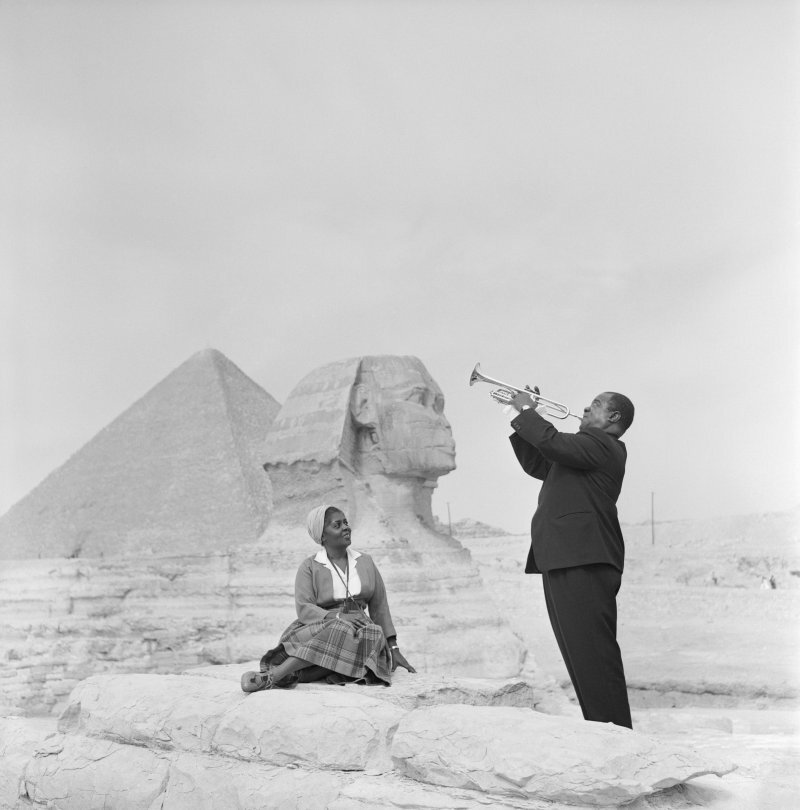 american_jazz_trumpeter_louis_armstrong_plays_the_trumpet_while_his_wife_sits_listening_with_the_sphinx_and_one_of_the_pyramids_behind_her_during_a_visit_to_the_pyramids_at_giza.jpg