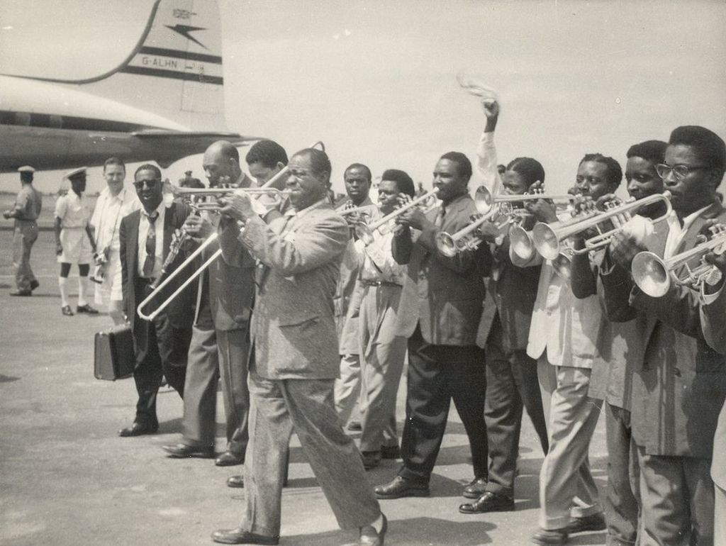 armstrong_greeted_by_nine_local_trumpet_players_at_airport_accra_the_gold_coast_ghana_1956.jpg