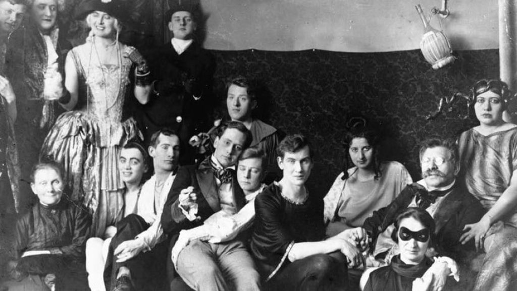 a_party_at_the_institute_for_sexual_science_is_shown_here_magnus_hirschfeld_second_from_right_is_the_one_with_the_moustache_and_glasses_his_partner_karl_giese_is_holding_his_hand.jpg