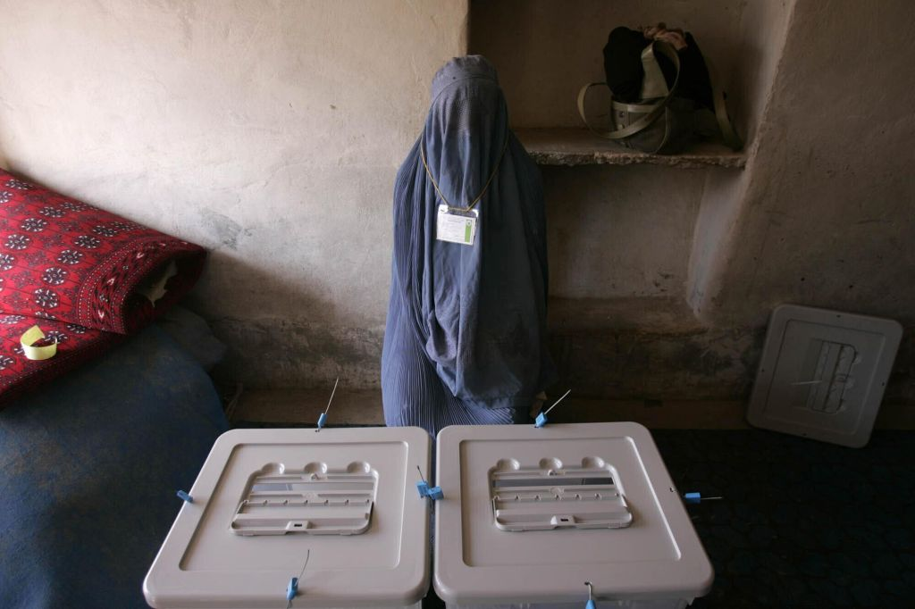 a_woman_poll_worker_waits_for_voters_to_arrive_at_a_polling_station_in_kandahar_afghanistan_sept_18_2005_afghanistan_held_landmark_parliamentary_elections_the_first_in_three_decades.jpg