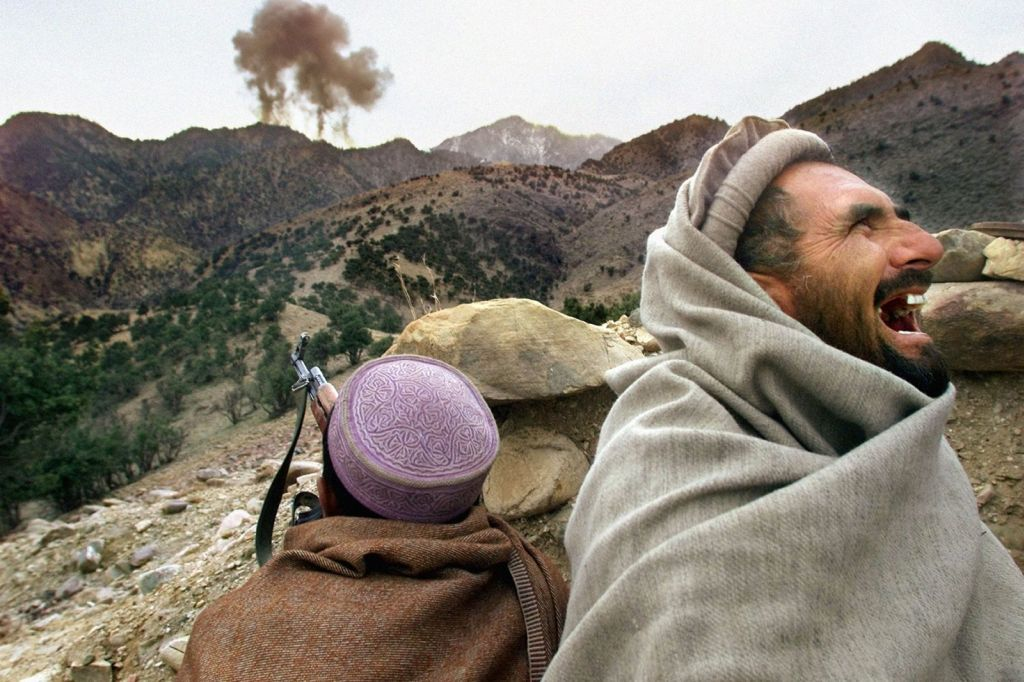 an_afghan_northern_alliance_fighter_bursts_into_laughter_as_us_planes_strike_a_taliban_position_near_tora_bora_afghanistan_in_december_2001.jpg