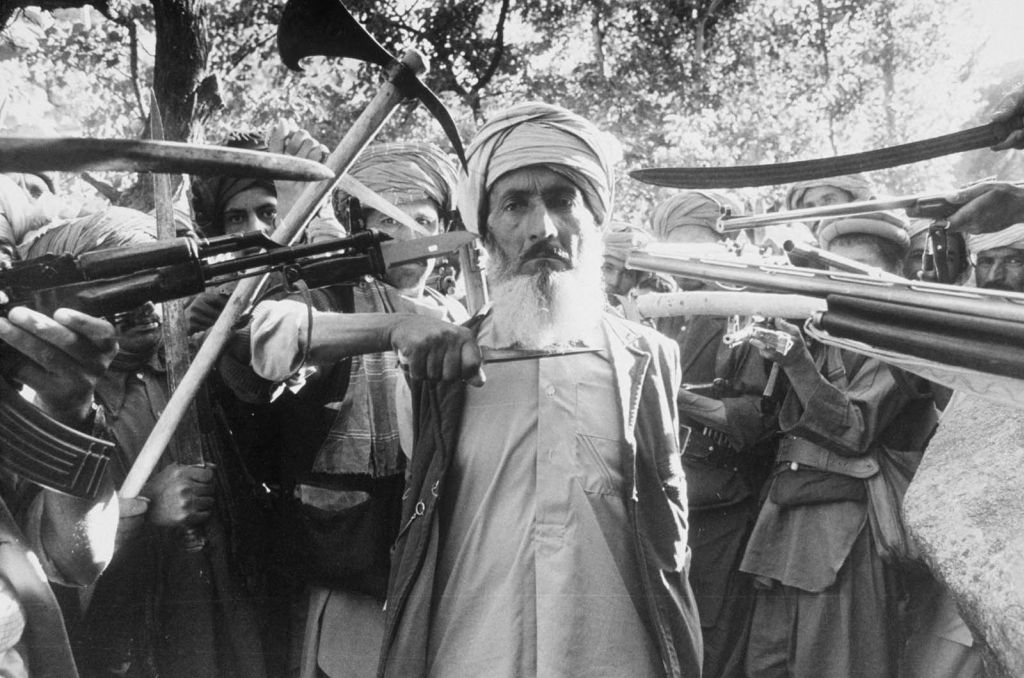 condemned_by_an_islamic_war_tribunal_for_denouncing_nine_families_a_man_is_escorted_20_km_outside_kabul_for_execution_1980.jpg