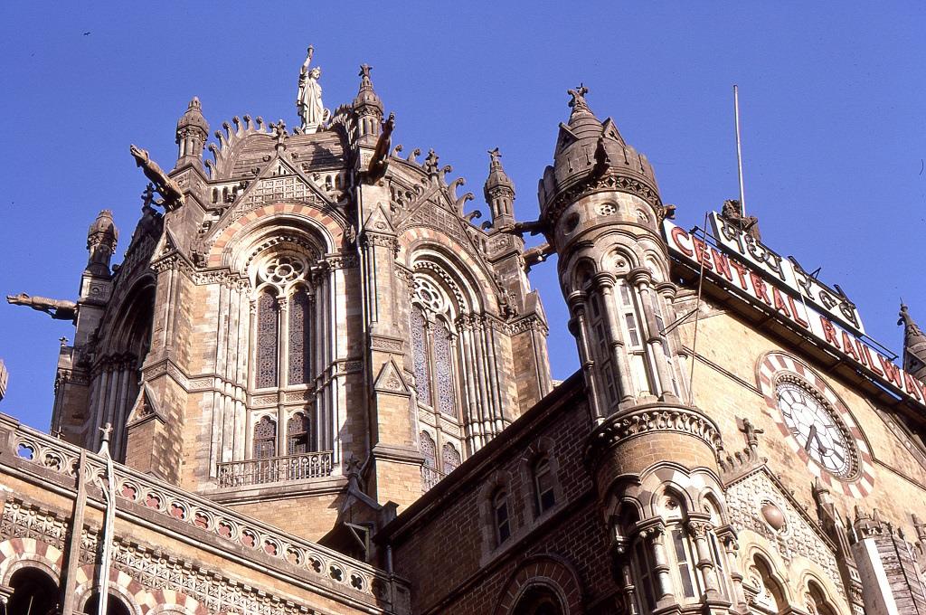 A Bombay-i (mára újba Mumbai) központi pályaudvar épületének részlete. A város bennszülött nevét a portugál hódítók értelmezték félre saját nyelvük etimológiája szerint (Bom Bahia portugálul Jó Öböl), ennek angolosítása lett a Bombay, amit 1995-ig használtak azóta újra a régi városnév a hivatalos.