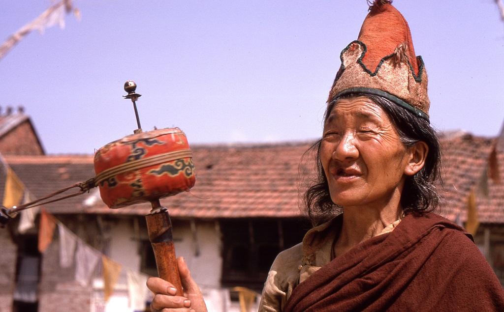 Bodhnath, Katmandu. Idős buddhista szerzetes imamalmával. Az imamalom vagy imakerék forgatásával felgyorsítható a kimondott mantrák száma, hiszen a vallásukban egyenértékű azzal.