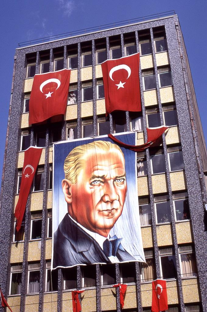Kemal Atatürk portréja és nemzeti zászlók Samsunban egy modern lakóház homlokzatán