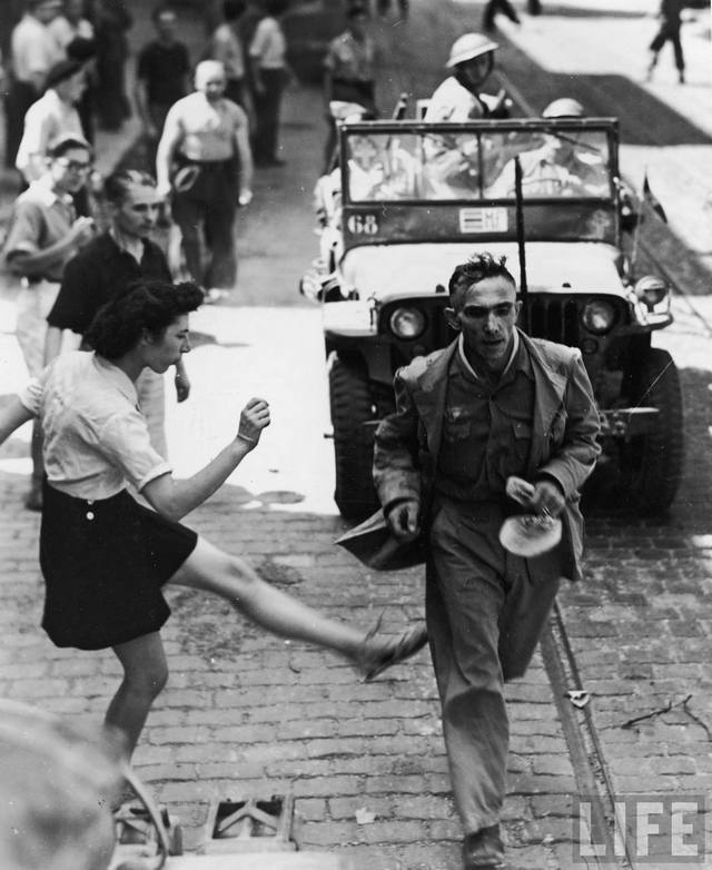 1944_szeptember_26_franciaorszag_fiatal_lany_billenti_fenekbe_a_varosukon_athalado_amerikaiak_altal_kisert_nemet_foglyot.jpg