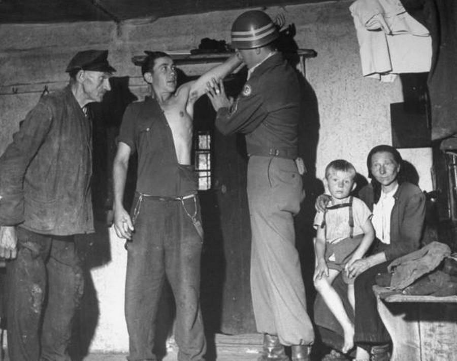 1946_amerikai_katonai_rendorseg_egykori_ss-tagokra_vadaszo_egysege_ellenorzi_egy_nemet_farmer_karjat_hogy_van-e_rajta_ss_tetovalas.jpg