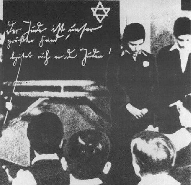 1935_two_jewish_pupils_in_a_german_school_are_humiliated_before_their_classmates_the_inscription_on_the_blackboard_reads_the_jew_is_our_greatest_enemy_beware_of_the_jew.jpg