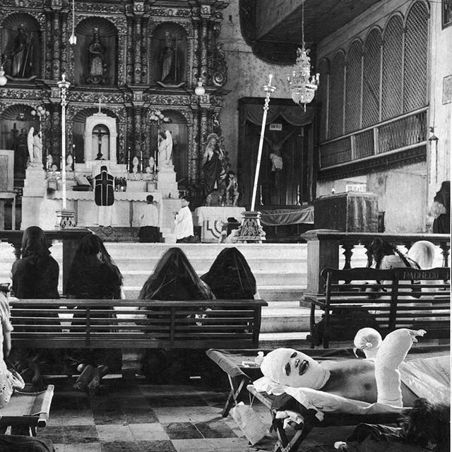 1944_badly_burned_u_s_officer_lies_on_his_hospital_stretcher_in_a_church_in_leyte_while_there_is_a_mass_going_on_the_church_worked_as_a_temporary_hospital_philippines.jpg