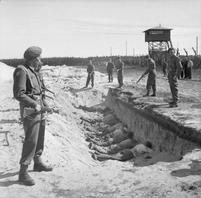 1945_german_ss_guards_exhausted_from_their_forced_labour_clearing_the_bodies_of_the_dead_are_allowed_a_brief_rest_by_british_soldiers_but_are_forced_to_take_it_by_lying_face_down_in_one_of_the_empty_mass_graves.jpg