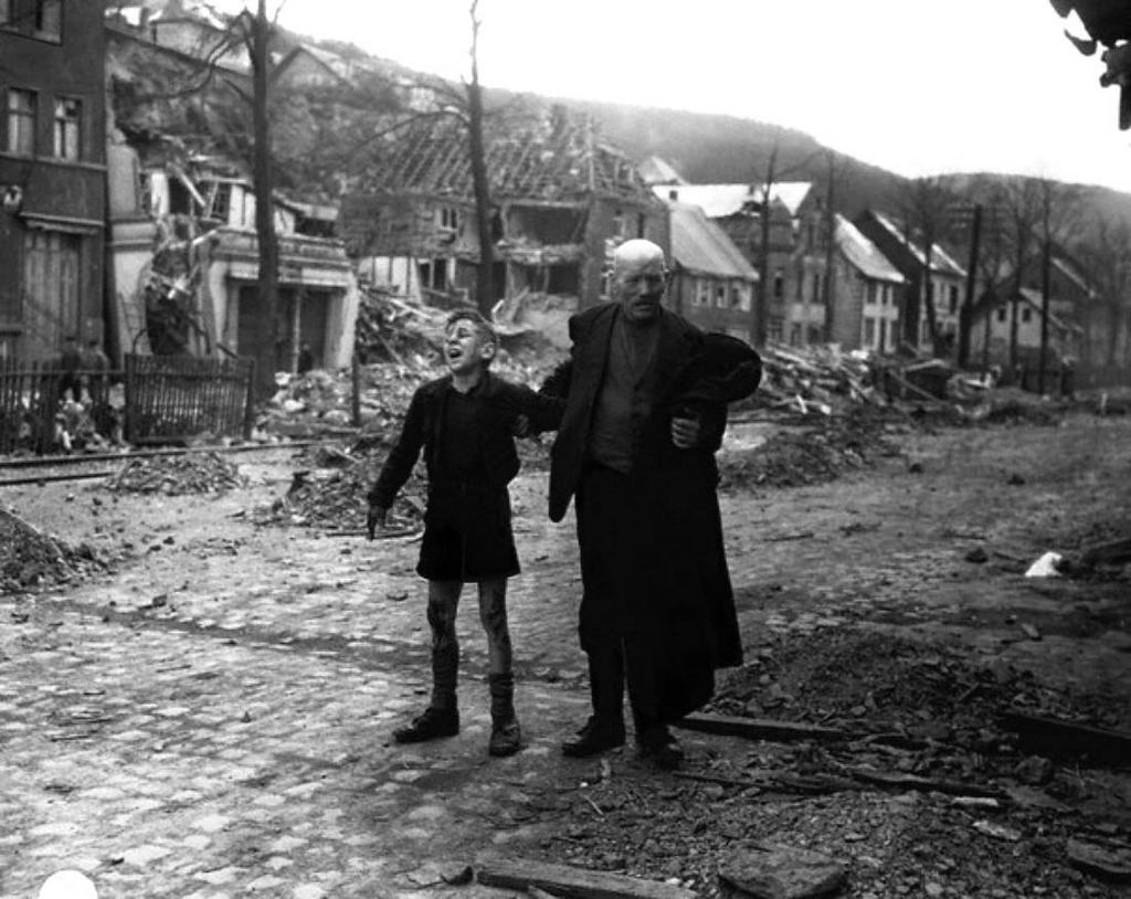 1945_german_man_rushes_a_young_boy_screaming_in_pain_to_an_allied_aid_station_after_the_boy_picked_up_a_pair_of_shoes_that_booby_trapped_with_explosives_by_retreating_ger_soldiers_altenbunnen.jpg