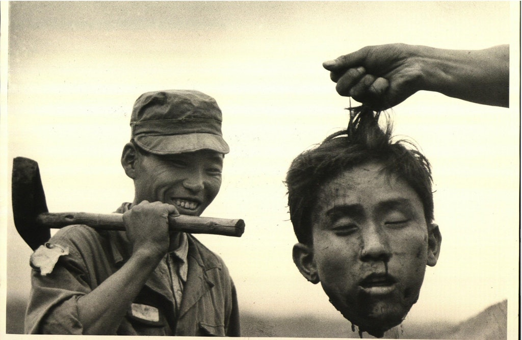 1952_hand_of_unseen_south_korean_holding_severed_head_of_north_korean_communist_guerrilla_by_his_hair_as_a_member_of_the_south_korean_national_police_smiles_broadly_with_an_axe_over_his_shoulder.jpg