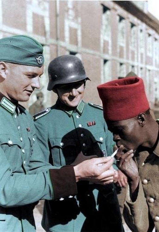 1940_two_members_of_the_german_schutzpolizei_light_a_french_colonial_soldier_s_cigarette.jpg