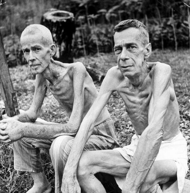 1945_two_emaciated_american_civilians_lee_rogers_john_c_todd_sit_outside_gym_which_had_been_used_as_a_japanese_prison_camp_manila_luzon_philippines.jpg