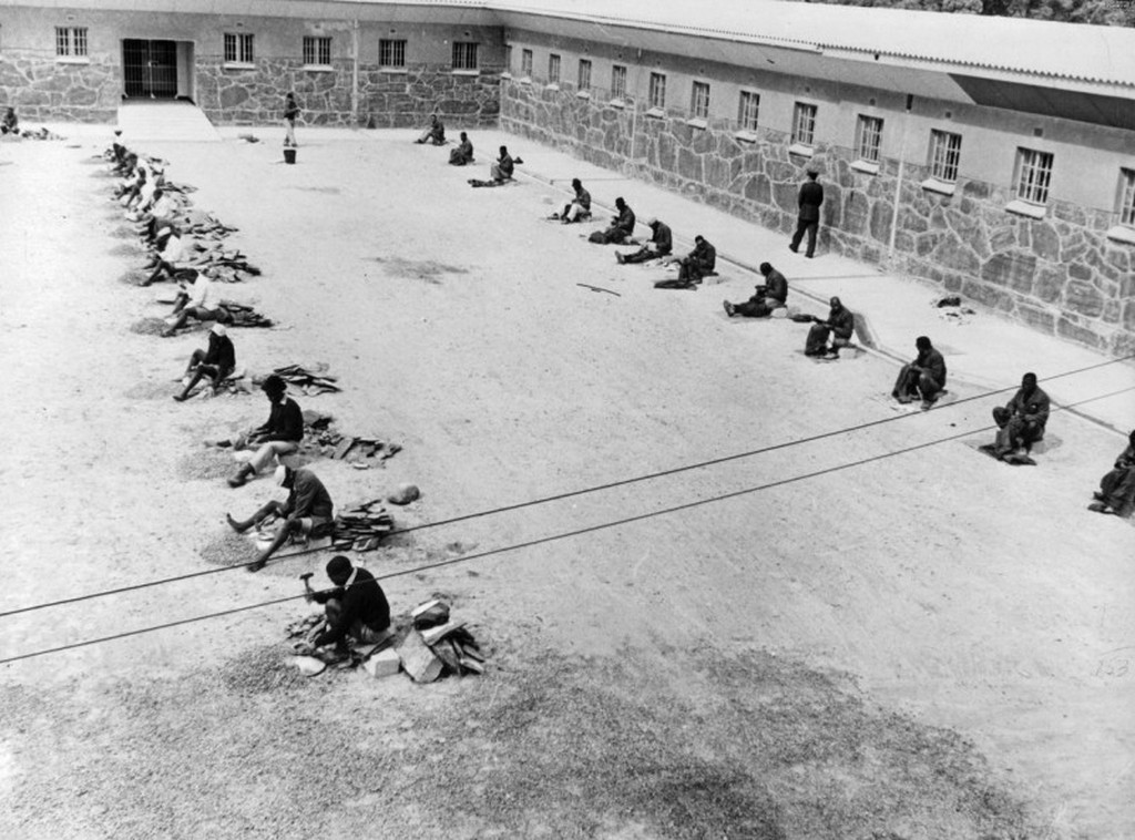 1964_prisoners_line_up_in_the_robben_island_prison_yard_one_line_prisoners_break_bigger_rocks_into_smaller_ones_and_the_right_line_prisoners_sew_prison_clothes_in_robben_island_south_africa.jpg