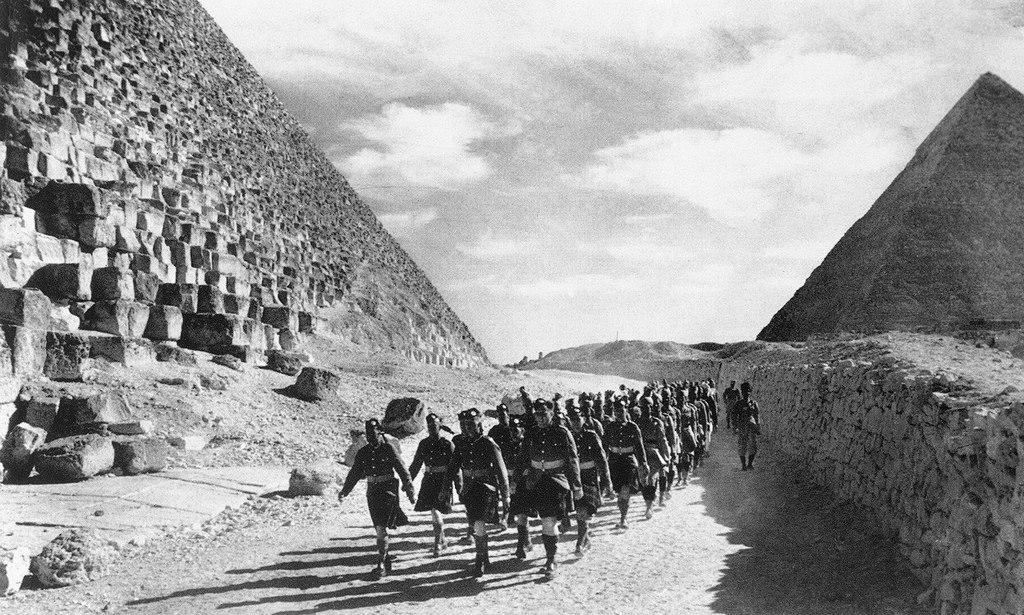 1940_a_scottish_infantry_regiment_of_the_british_army_and_indian_troops_march_past_the_great_pyramid_in_the_north_african_desert.jpg