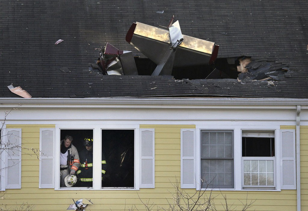 2017_02_28_firefighters_investigate_the_scene_after_a_small_plane_crashed_into_the_roof_of_a_condominium_building_across_the_merrimack_river_from_lawrence_municipal_airport_in_methuen_massachusetts.jpg