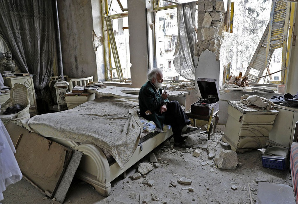 2017_03_20_abu_omar_70_smokes_his_pipe_as_he_sits_in_his_destroyed_bedroom_listening_to_music_on_his_hand-cranked_gramophone_in_aleppo_syria.jpg