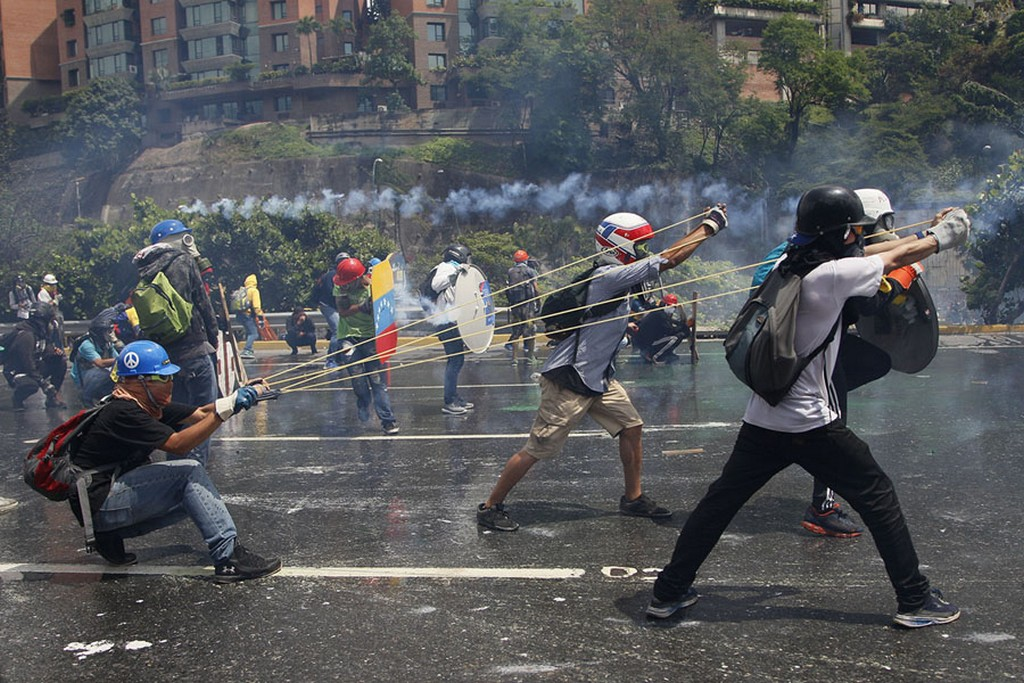2017_05_10_anti-government_protesters_work_together_to_aim_a_giant_slingshot_holding_a_glass_bottle_of_fecal_matter_at_security_forces_blocking_their_march_from_reaching_the_supreme_court_in_caracas_venezuela.jpg