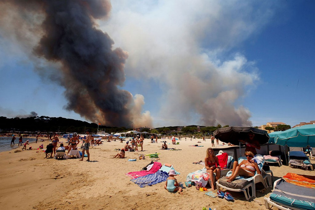 2017_07_26_smoke_fills_the_sky_above_a_burning_hillside_as_tourists_relax_on_the_beach_in_bormes-les-mimosas_france.jpg
