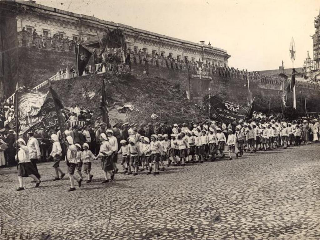 1920_elso_vilaghaborus_gyozelmi_parade_moszkvaban_a_voros_teren_a_hatterben_az_osi_szokasra_visszavezetheto_gyozelmi_kurganon_allo_tribun_a_kurgan_zsakmanyolt_eszkozokbol_targyakbol_epult_mint_torott_fegyverek_zaszlorud.jpeg