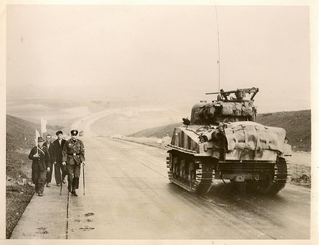 1945_amerikai_tank_halad_el_a_nemet_autobahn-on_kassel_tersegeben_egy_csapat_feher_zaszlot_vivo_hazafele_tarto_nemet_katona_mellett.png