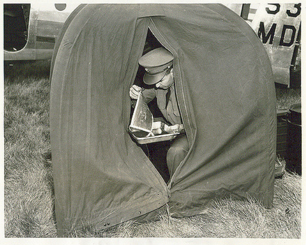 1941_a_sergeant_from_the_photo_section_of_an_army_air_corps_observation_squadron_developing_a_print_in_a_portable_field_darkroom.png