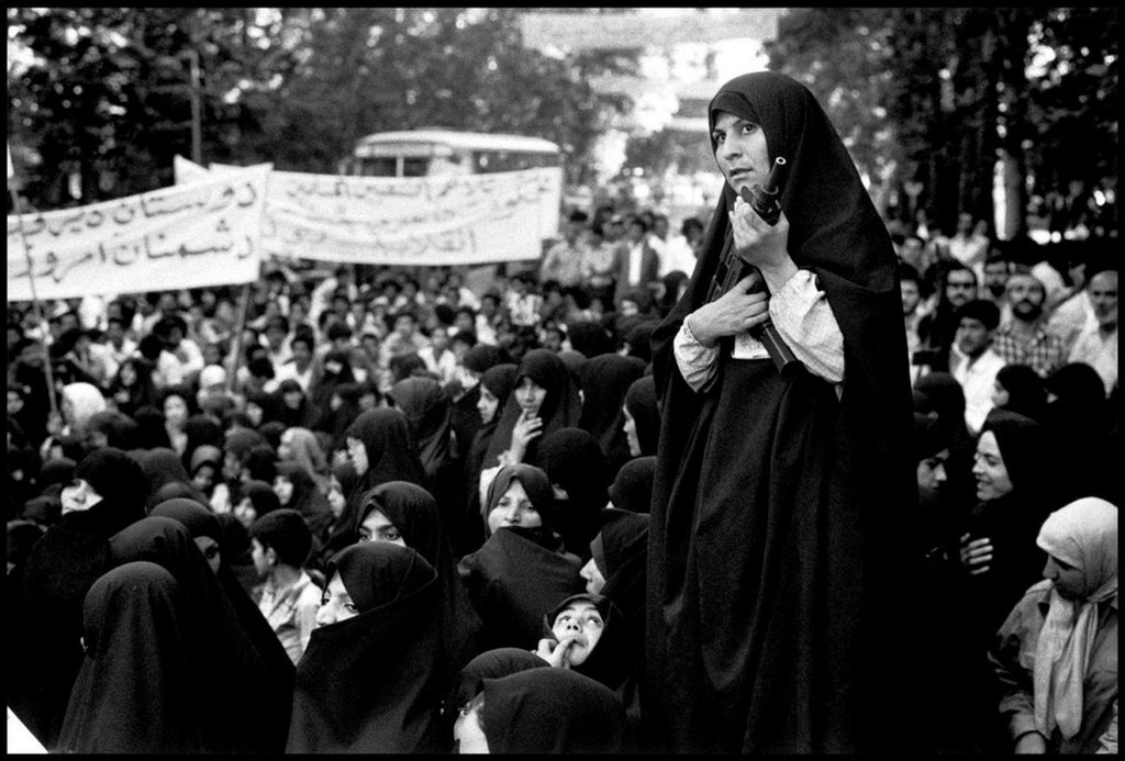 1979_junius_teheran_iran_a_chador_clad_militia_woman_armed_with_a_uzi_submachine_gun_controls_a_demonstration_against_iraq.jpg