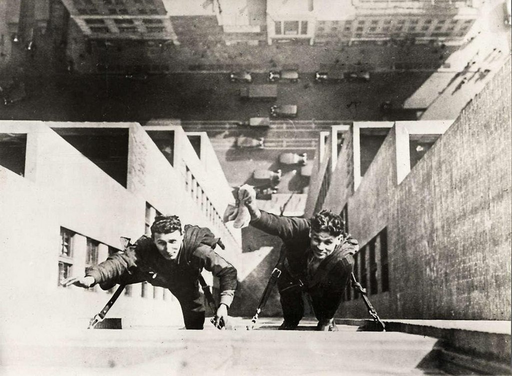 1930_two_window_cleaners_wave_to_the_camera_on_the_41st_floor_of_a_skyscraper.jpg