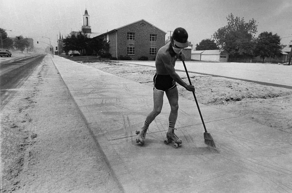 1980_a_man_in_spokane_roller_skates_while_sweeping_volcanic_ash_from_the_explosion_of_mount_st_helens_in_washington.jpg