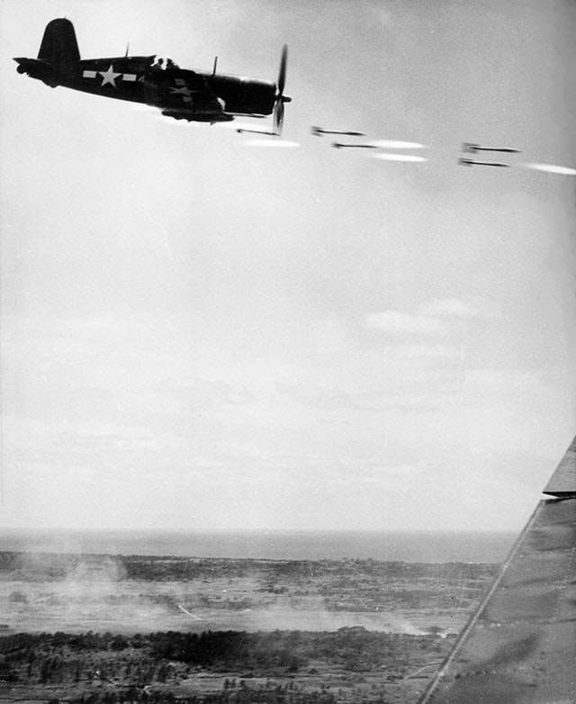 1945_junius_vought_f4u-1_corsair_firing_its_load_of_ffar_rocket_projectiles_on_a_run_against_a_japanese_stronghold_on_okinawa.jpg