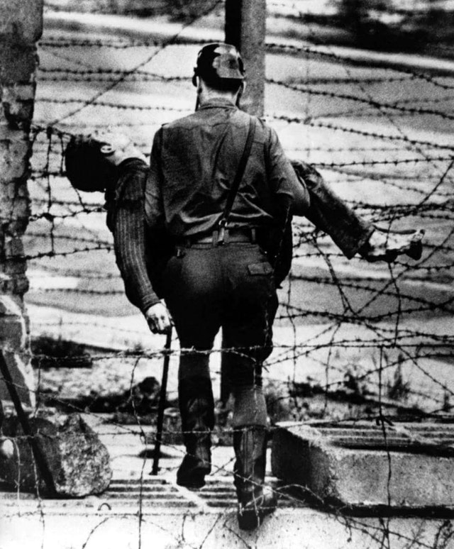 1962_east_german_guard_removes_the_body_of_peter_fichter_killed_trying_to_escape_to_west_berlin.jpg