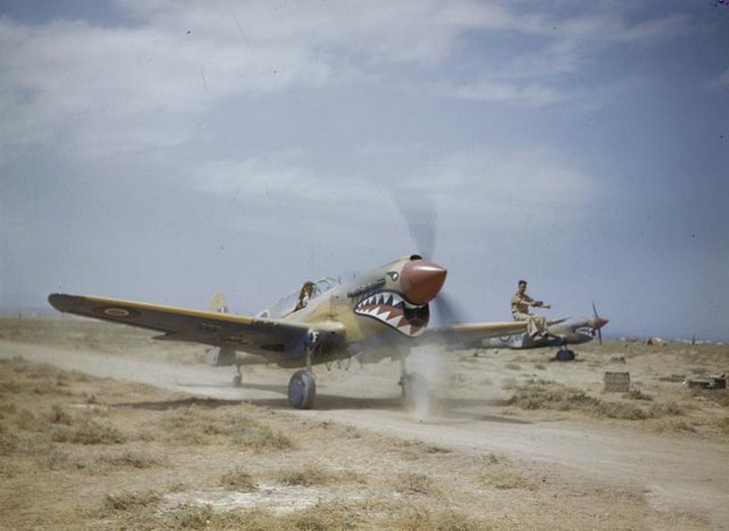 1943_curtiss_kittyhawk_mark_iii_royal_air_force_taxiing_through_the_scrub_at_medenine_tun_ground_crewman_on_the_wing_is_directing_the_pilot_whose_view_ahead_is_hindered_by_the_aircraft_s_nose_while_the_tail_is_down.jpg
