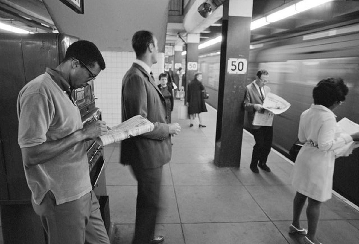 1968_arthur_ashe_doing_a_crossword_puzzle_while_waiting_for_the_subway_completely_unrecognized_the_day_after_he_won_the_u_s_open_men_s_singles_championship.jpg