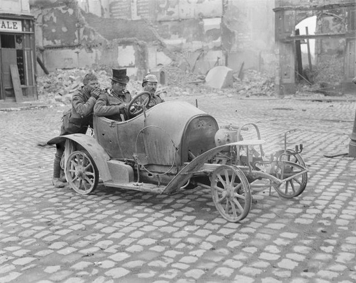 1918_three_british_soldiers_amusing_themselves_in_cambrai_france_with_the_remains_of_a_motor_car.jpg