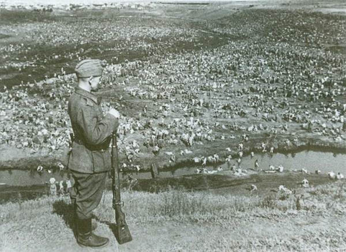 1942_a_bored_german_sentry_gazes_over_an_entire_river_valley_of_captured_soviet_prisoners_belorussia.jpg