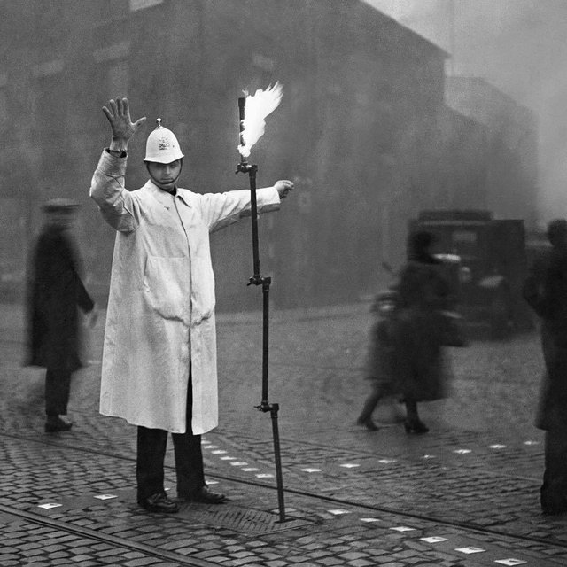 1935_a_police_officer_directing_traffic_in_london_s_fog_with_the_help_of_an_apparatus_connected_with_the_gas_main_that_can_be_folded_up_and_put_in_a_metal_box_sunk_in_the_street.jpg