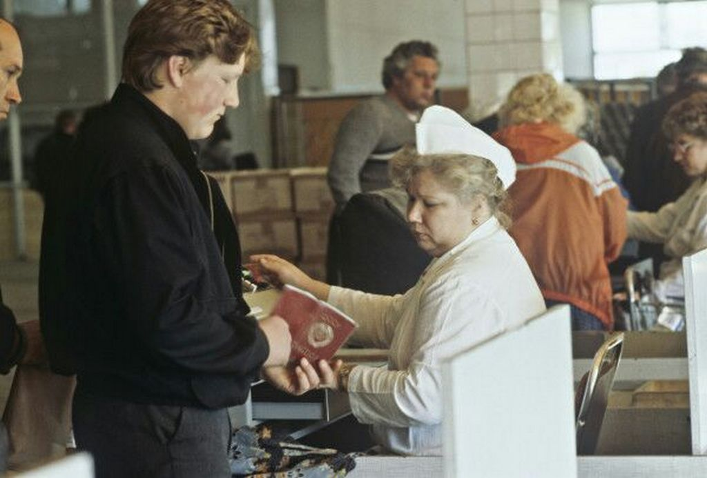 1990_a_penztaros_ellenorzi_a_vevot_egy_moszkvai_tartozkodasi_engedellyel_kapcsolatban.jpeg