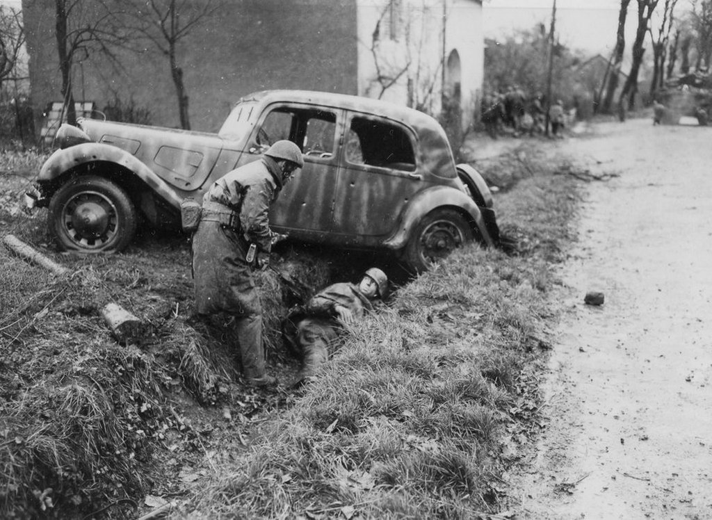 1944_november_20_a_soldier_of_the_2nd_battalion_de_choc_french_commandos_takes_a_german_prisoner_behind_a_shattered_staff_car_during_a_firefight_in_belfort_france.jpg