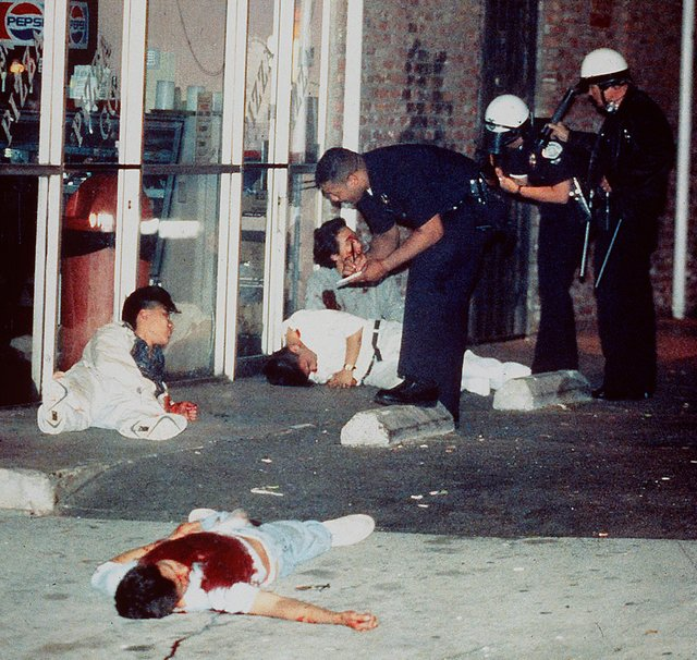 1992_police_officers_questioned_three_injured_koreans_in_los_angeles_while_the_fourth_korean_seen_in_the_foreground_laid_dead_in_his_bloodied_shirt_after_being_shot_while_trying_to_protect_the_parlor_during_the_u.jpg