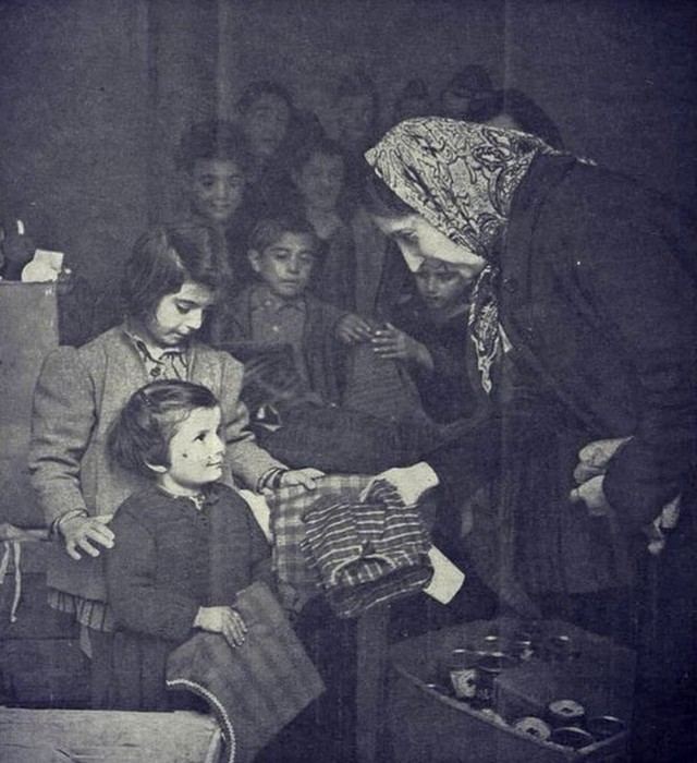 1942_syrian_woman_distributing_food_and_clothes_to_greek_refugees_in_syria_cr.jpg