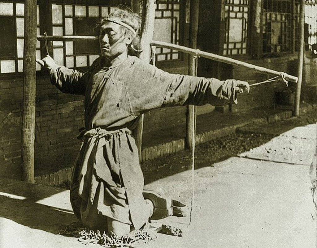 1906_chinese_justice_prisoner_kneeling_on_chains_little_fingers_supporting_arms_moukden.jpg