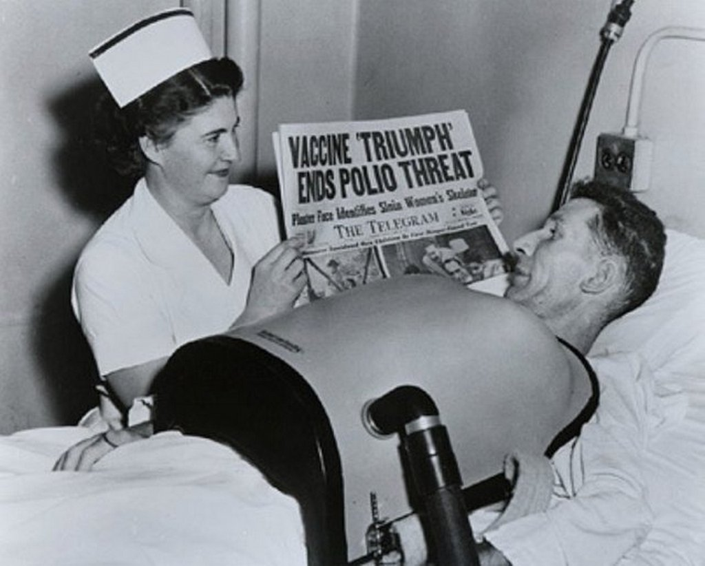 1955_nurse_showing_newspaper_headline_about_polio_vaccine_to_a_man_on_chest_respirator_due_to_polio.jpg