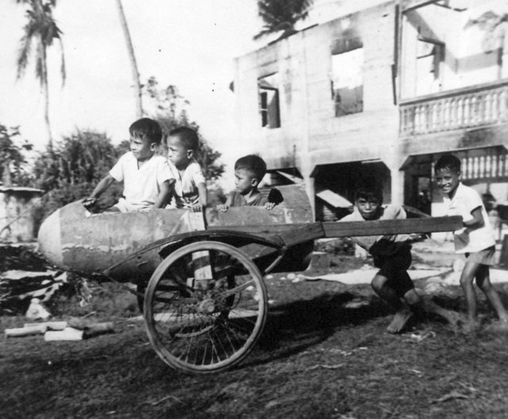 1945_majus_a_japanese_bomber_s_belly_tank_is_mounted_on_wheels_and_used_as_a_plaything_by_guam_children.jpg