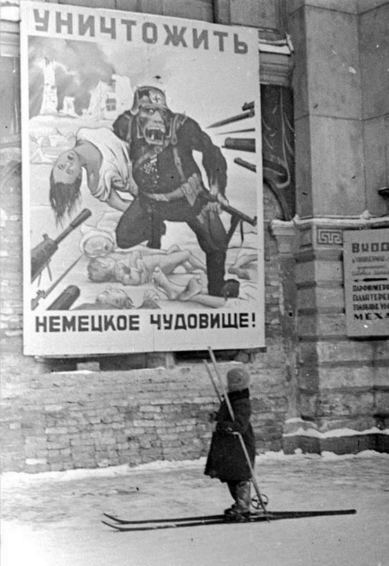 1941_december_a_russian_child_on_skis_reads_a_soviet_propaganda_poster_stating_kill_german_monster_leningrad_su.jpg