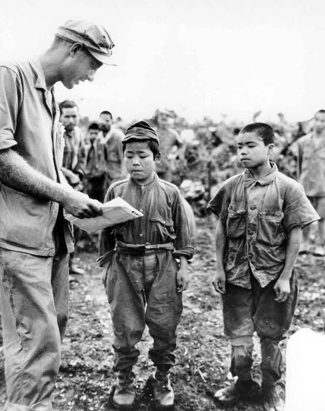 1945_marine_first_lieutenant_hart_h_spiegal_of_topeka_kansas_uses_sign_language_as_he_tries_to_strike_up_a_conversation_with_two_tiny_japanese_soldiers_captured_on_okinawa.jpg