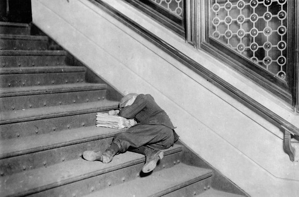 1912_a_young_newsboy_asleep_on_a_set_of_stairs_with_his_papers_in_jersey_city_new_jersey.jpg