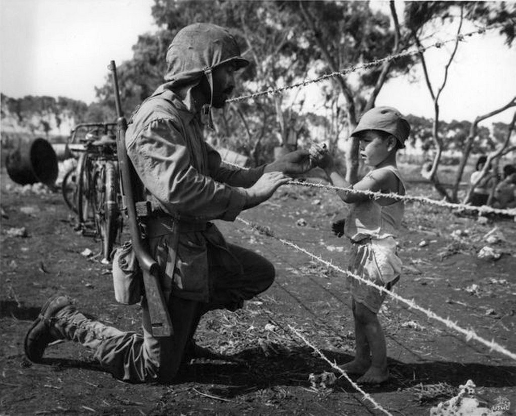 1944_us_marine_giving_an_interned_child_candy_tinian_mariana_islands.jpg